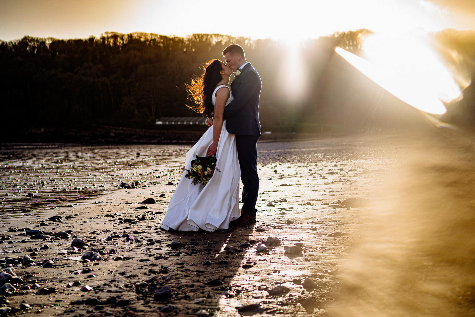 bride and groom kissing on the beach at sunset with Oxwich Bay Hotel in the background
