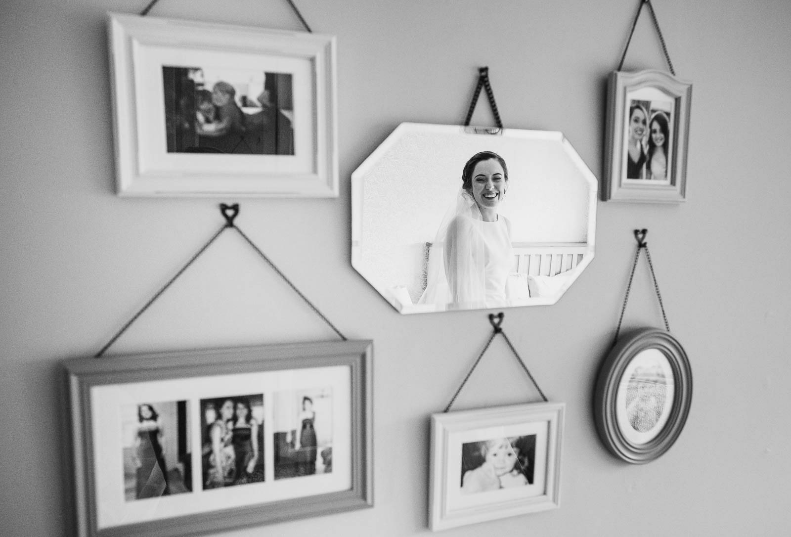 smiling bride reflected in mirrors with photographs of her with her sister
