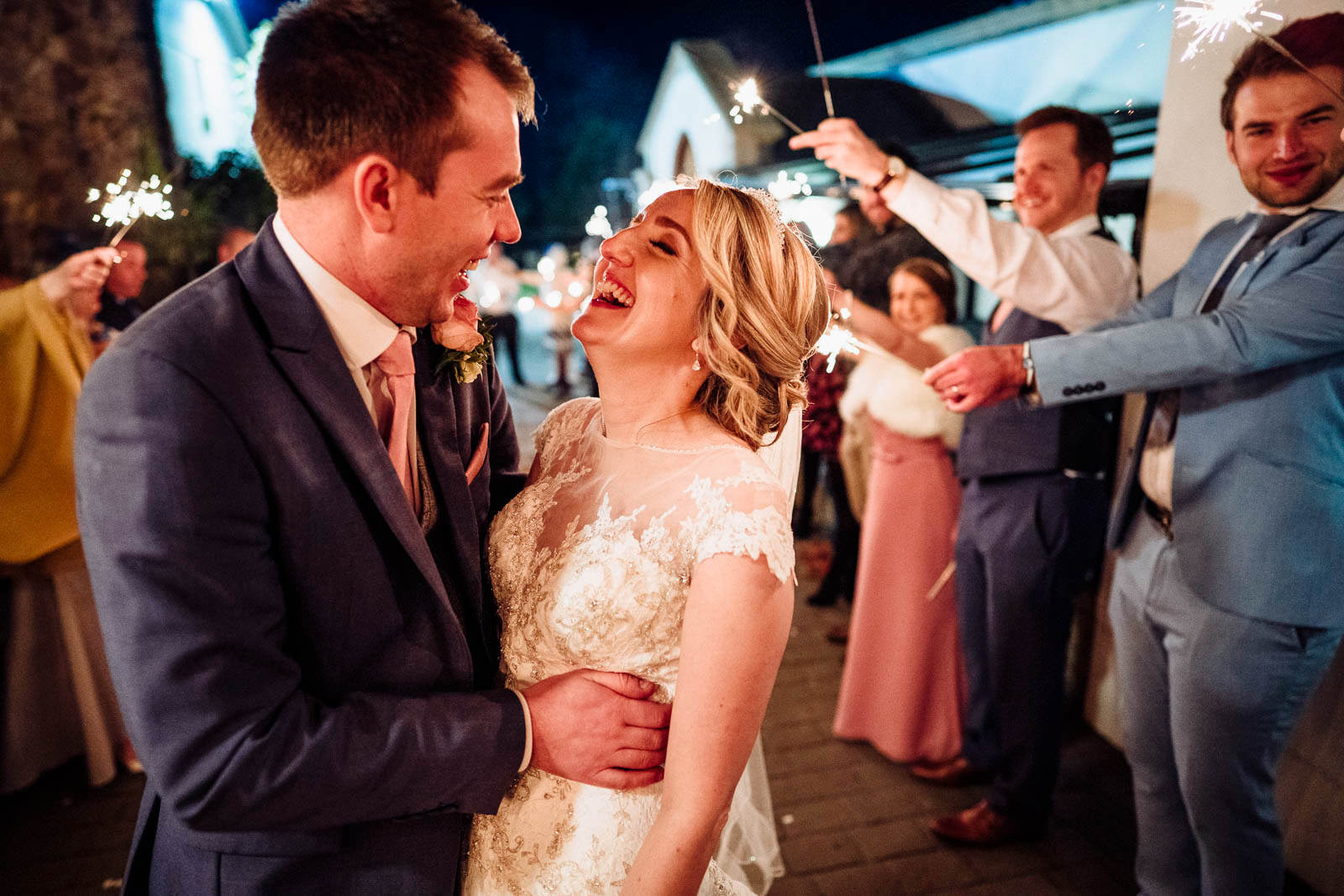 laughing bride and groom during a sparkler exit at the King Arthur Hotel in Gower, Swansea, South Wales