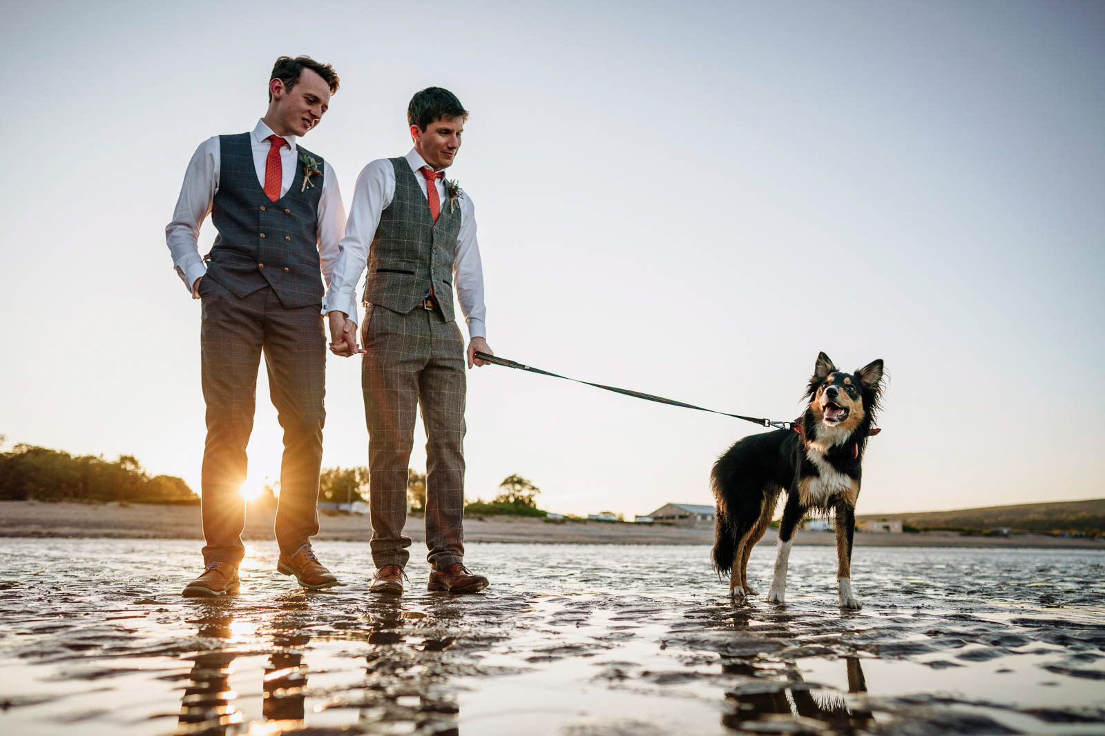 two grooms and their dog on Oxwich Bay beach, same sex wedding at Oxwich Bay Hotel