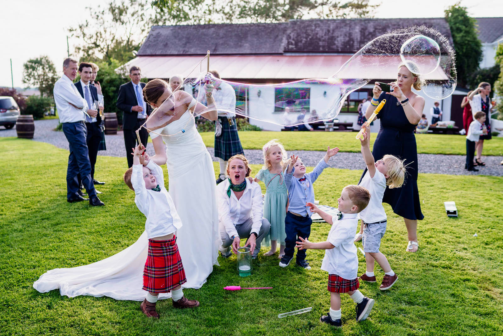 bride plays with giant bubbles for children at her wedding at Jabajak Vineyard in West Wales
