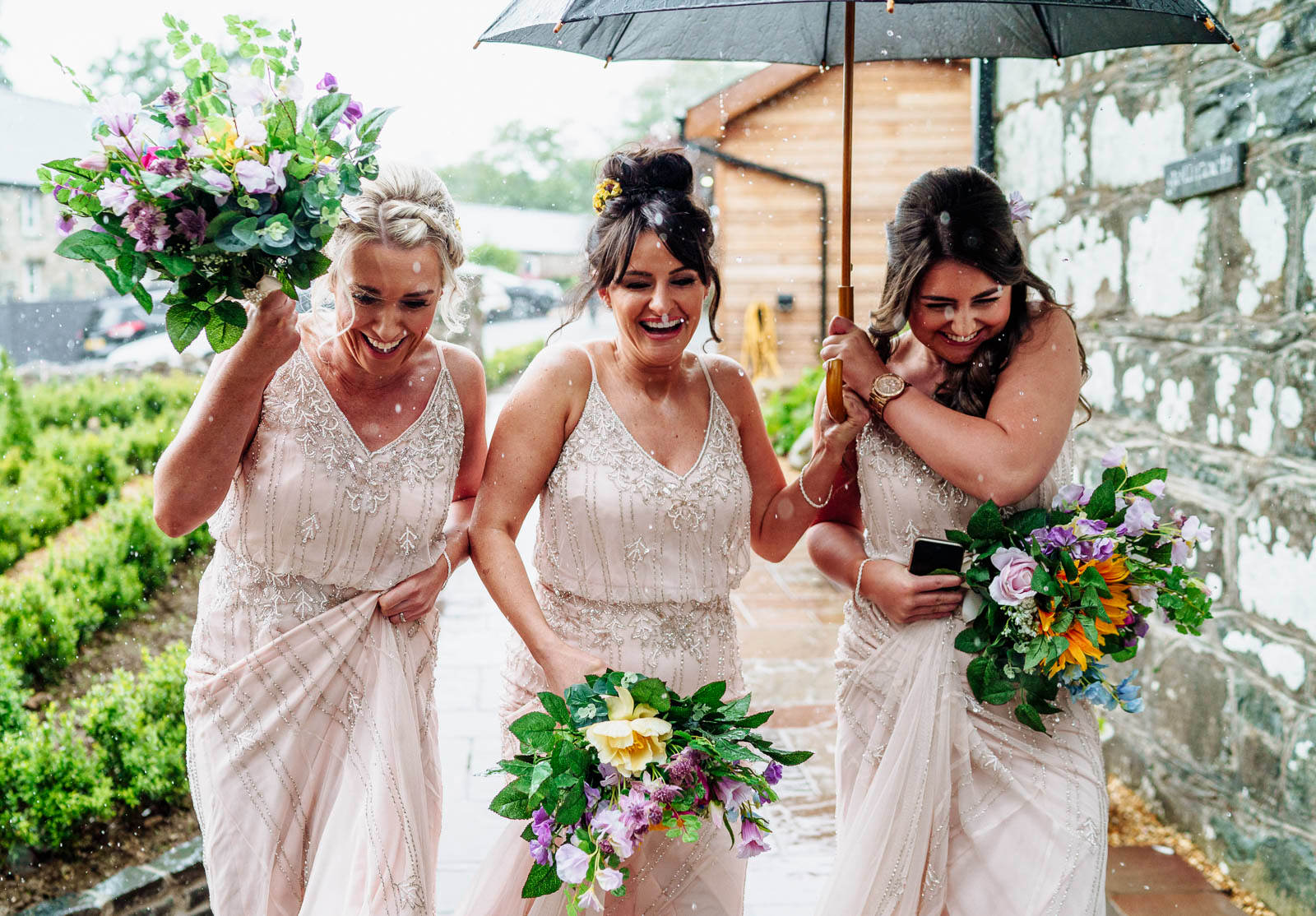 three bridesmaids run for cover in the pouring rain at Gellifawr Woodland Retreat in West Wales