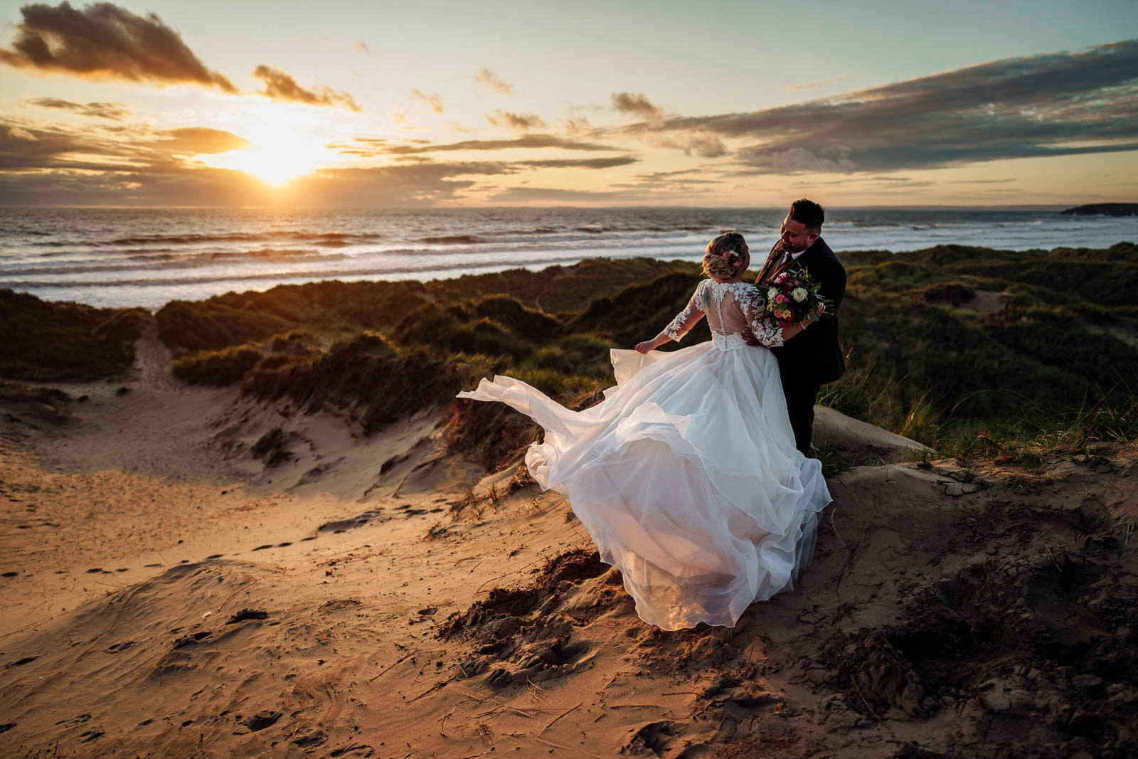 Bride and groom watch the sunset together at Llangennith beach, Gower, South Wales